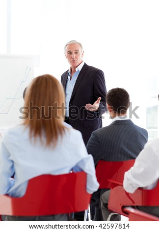 Senior businessman giving a conference to young business people