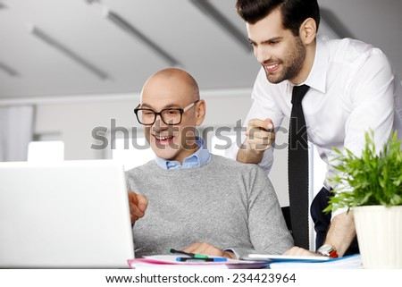 Senior businessman giving advise to his colleagues while writing annual report on laptop.  - stock photo