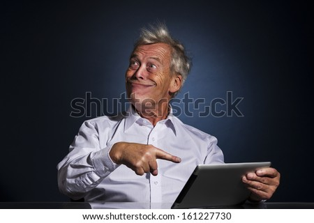 Senior businessman grinning with a look of fatuous self-satisfaction and pointing to his tablet computer with his finger as though indicating a great personal achievement, comic studio portrait - stock photo