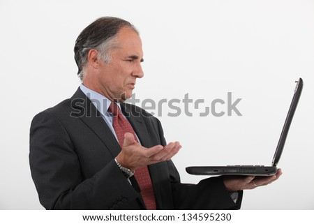 Senior businessman having technical issues with laptop - stock photo
