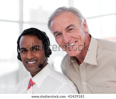 Senior businessman helping his colleague in the office - stock photo