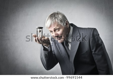 Senior businessman holding a hourglass - stock photo