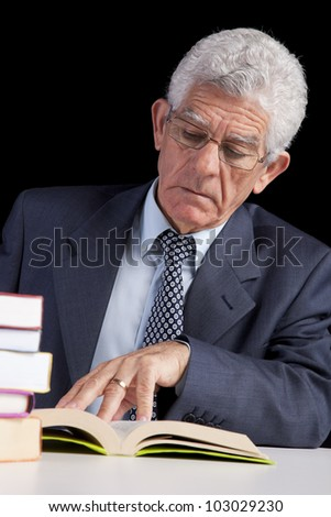 Senior businessman holding a page from an open book (isolated on black) - stock photo
