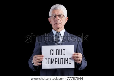 Senior businessman holding a paper with the Cloud Computing words (isolated on black)