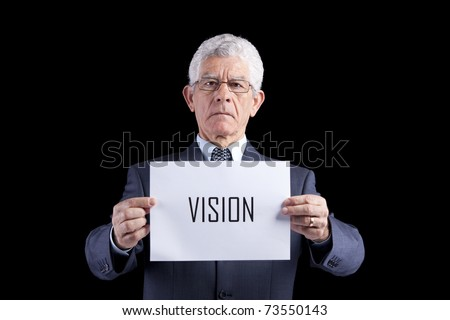 Senior businessman holding a paper with the Vision word (isolated on black) - stock photo