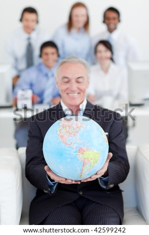 Senior businessman holding a terrestrial globe with his colleagues in the background