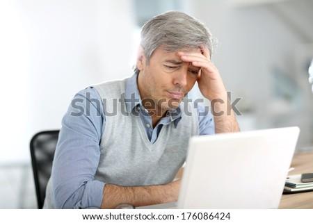 Senior businessman in front of laptop having a headache - stock photo