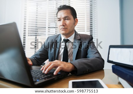 Senior Businessman in grey suit sitting and using laptop at his workplace. Copy space.