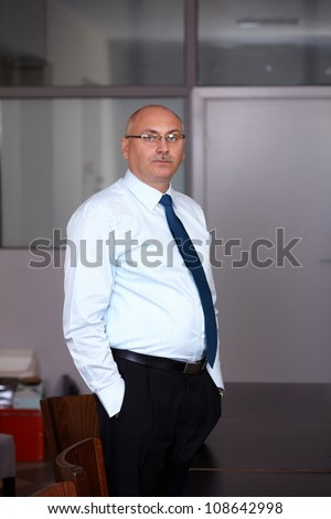 Senior businessman in his office, hands in pockets