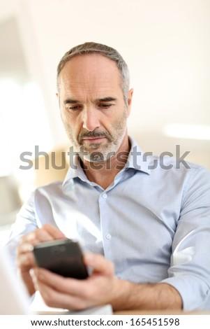 Senior businessman in office using smartphone - stock photo