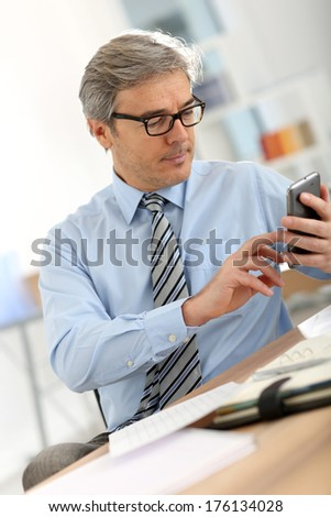 Senior businessman in office using smartphone - stock photo