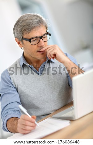 Senior businessman in office working on laptop - stock photo