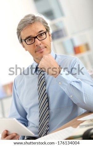 Senior businessman in office working on tablet - stock photo