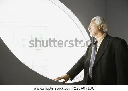 Senior businessman looking out window - stock photo