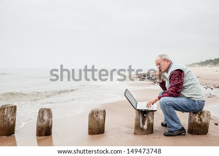Senior businessman on beach working with notebook on a foggy day - stock photo