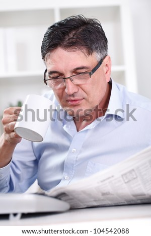 Senior businessman on coffee break in office lobby, reading papers, holding coffee cup, - stock photo