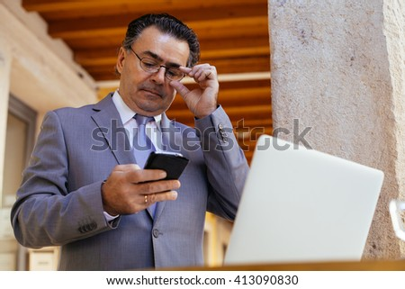 Senior businessman read text message on his smart phone while sitting in modern coffee shop with laptop computer. Caucasian man working outside during morning breakfast in cafe bar - stock photo