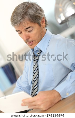 Senior businessman relaxing at work with tablet - stock photo