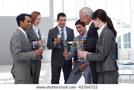 Senior businessman serving Champagne to his successful team in the office - stock photo