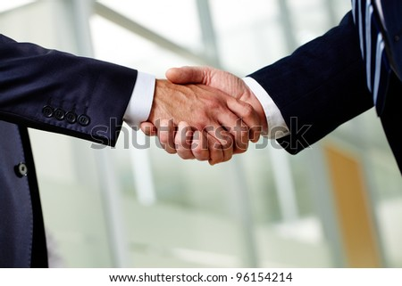 Senior businessman shaking hands as a sign of a successfully concluded deal - stock photo