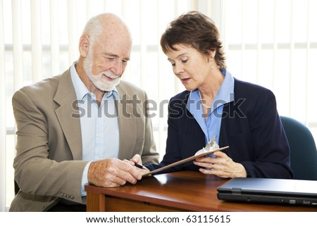 Senior businessman signs a contract with the assistance of a mature businesswoman.