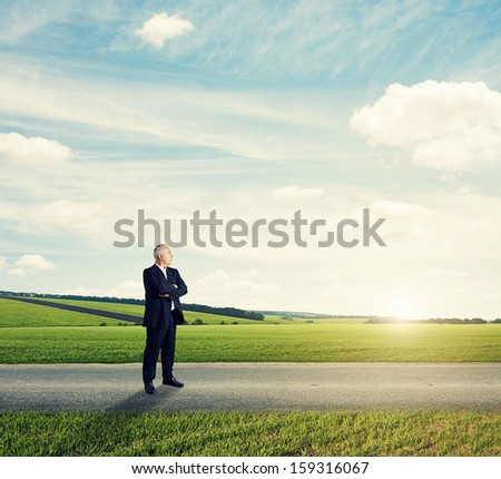 senior businessman standing on the road against green field