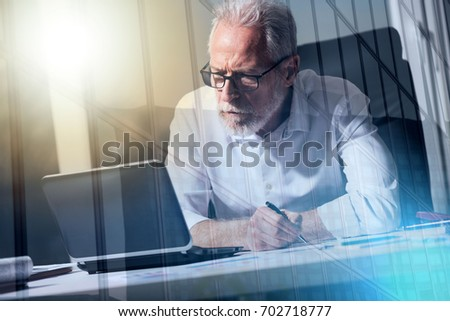 Senior businessman taking notes in office, light effect, double exposure