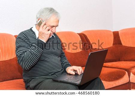 Senior businessman talking on cell phone and typing on laptop sitting on sofa. Concept photo of senior people and modern technology.
