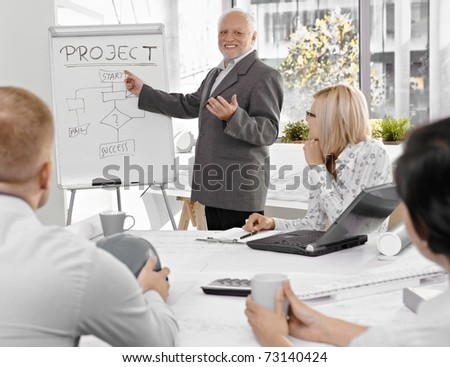 Senior businessman talking to colleagues, explaining project success, pointing at whiteboard, smiling.? - stock photo