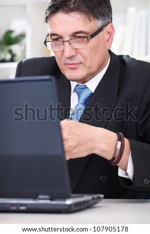 Senior businessman typing on laptop, concentrating on working - stock photo