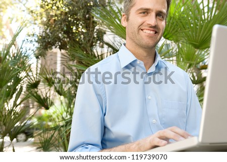 Senior businessman using a laptop computer while sitting on a bench in a city park, outdoors. - stock photo