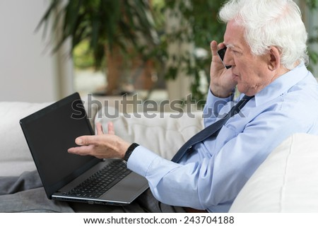 Senior businessman using laptop and talking on the phone - stock photo