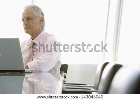 Senior businessman using laptop at conference table - stock photo