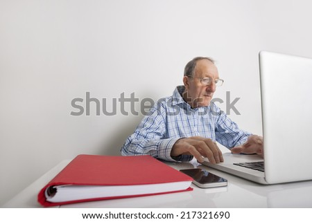 Senior businessman using laptop with book binder and cell phone on office desk - stock photo