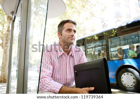 Senior businessman waiting for the bus at a bus stop in the city. - stock photo
