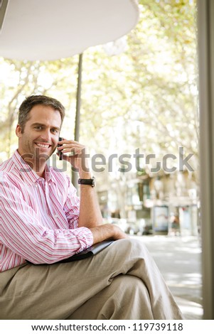 Senior businessman waiting for the bus at a bus stop in the city, using his cell phone and having a conversation. - stock photo