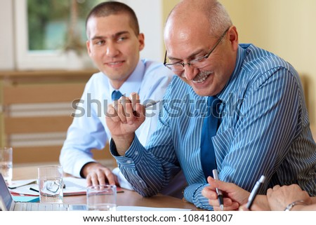 Senior businessman with junior colleague works on some paperwork