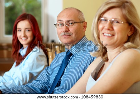 Senior businessman with two female colleagues, all looking to camera - stock photo