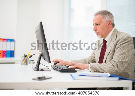 Senior businessman working on his computer - stock photo