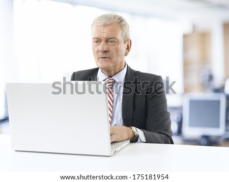 Senior businessman working on laptop at office.