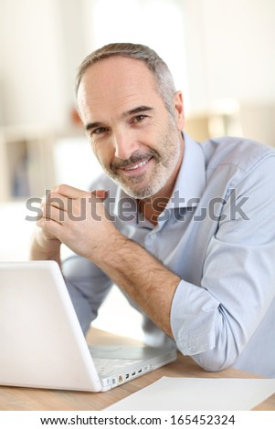 Senior businessman working on laptop computer - stock photo