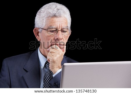 Senior businessman working with his laptop at his office - stock photo
