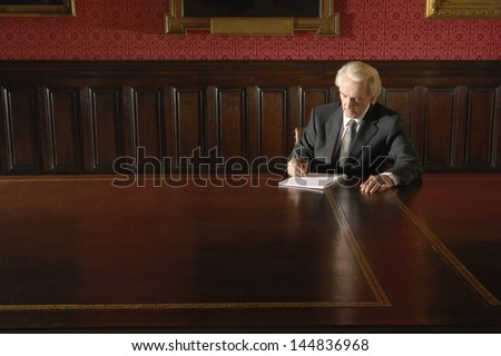 Senior businessman writing on book at conference table