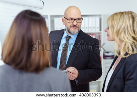Senior businesspeople in a meeting standing grouped around a flip chart having a serious discussion, focus to a balding man in glasses