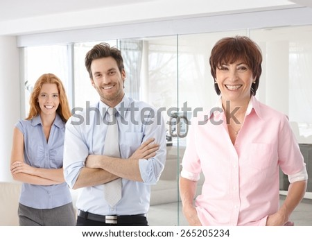 Senior businesswoman and young colleagues smiling happy at office. - stock photo