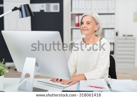 Senior businesswoman at work in the office seated at her desk typing in information on the desktop computer - stock photo