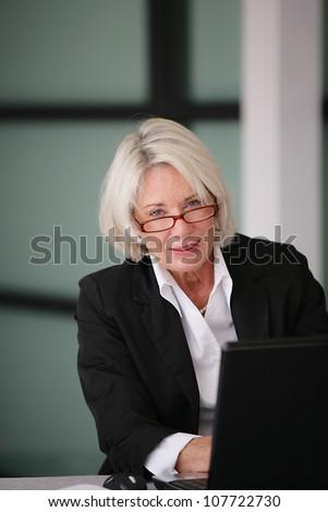 Senior businesswoman sending e-mails - stock photo