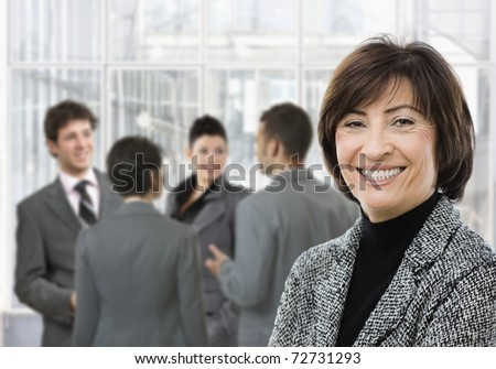 Senior businesswoman smiling, looking at camera, businesspeople in conversation in lobby.? - stock photo