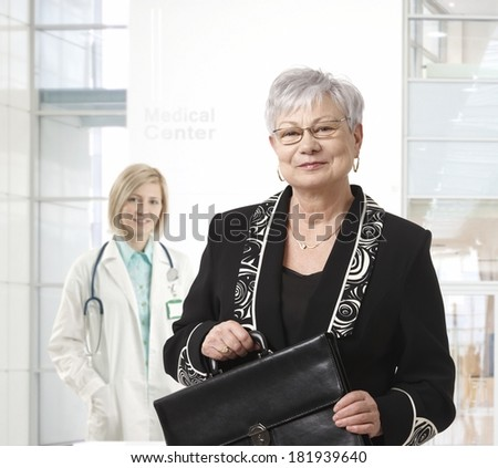 Senior businesswoman standing at medical center. - stock photo