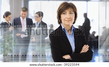 Senior businesswoman standing in corporate office,  businesspeople talking in background behind glass wall. - stock photo